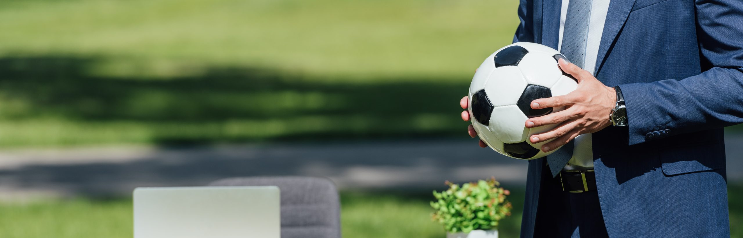 panoramic shot of businessman holding soccer ball in park near table with laptop